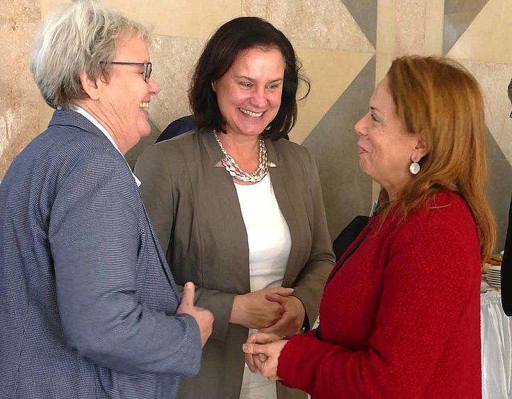 Drei Damen unterhalten sich. Lächeln, freundliche, offene, lockere Körperhaltungen