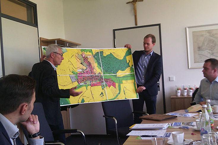 Zwei Männer halten einen Gemeindeplan so in ihren Händen. dass die Delegationsteilnehmer sie sehen können