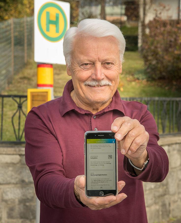 Mann hält vor einer Bushaltestelle sein Handy in die Kamera, auf dem die DorfBusApp zu sehen ist.