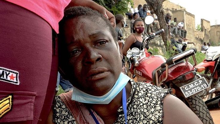 Eine Frau mit Maske unter dem Kinn blickt erschöpft und verstört drein und lehnt sich an jemandem an.