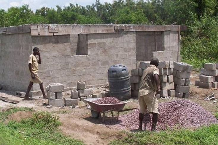 Zu sehen ist ein kleines eingeschossiges Steinhaus im Rohbau. Davor lädt ein Arbeiter kleine Steine in einen Schubkarren. Ein weiterer Mann kommt dazu.