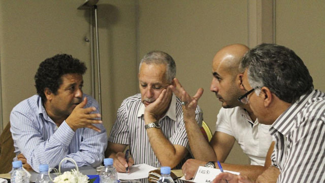 Vier Männer an einem Tisch sind in ein angeregtes Gespräch vertieft