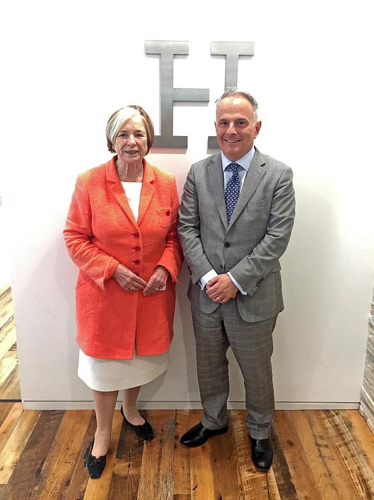 """Ursula Männle steht links neben einem älteren, lächelnden Herren in gedecktem Anzug. Hier ihnen an der Wand ein großes """"H"""" aus Silber oder Aluminium."""