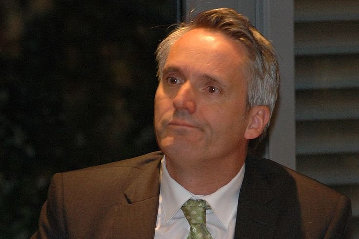 Mittelalter Mann mit weißem Hemd, grüner Krawatte und grauem Sakko zieht eine Grimasse des Missfallens