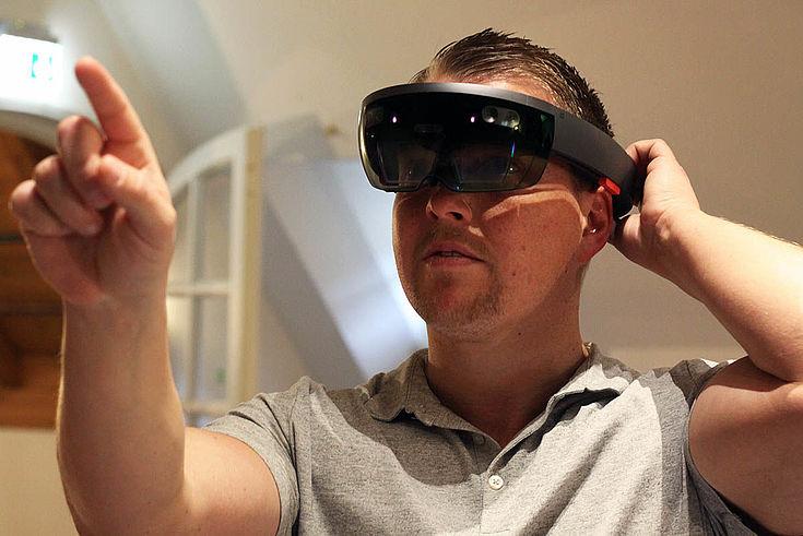 Junger Mann mit riesigen VR-Brille, der vor sich in die Luft deutet und offenbar gerade etwas bedient.