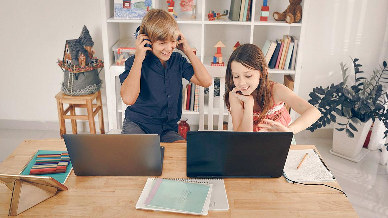 Junge und Mädchen machen Schule zu Hause am Laptop