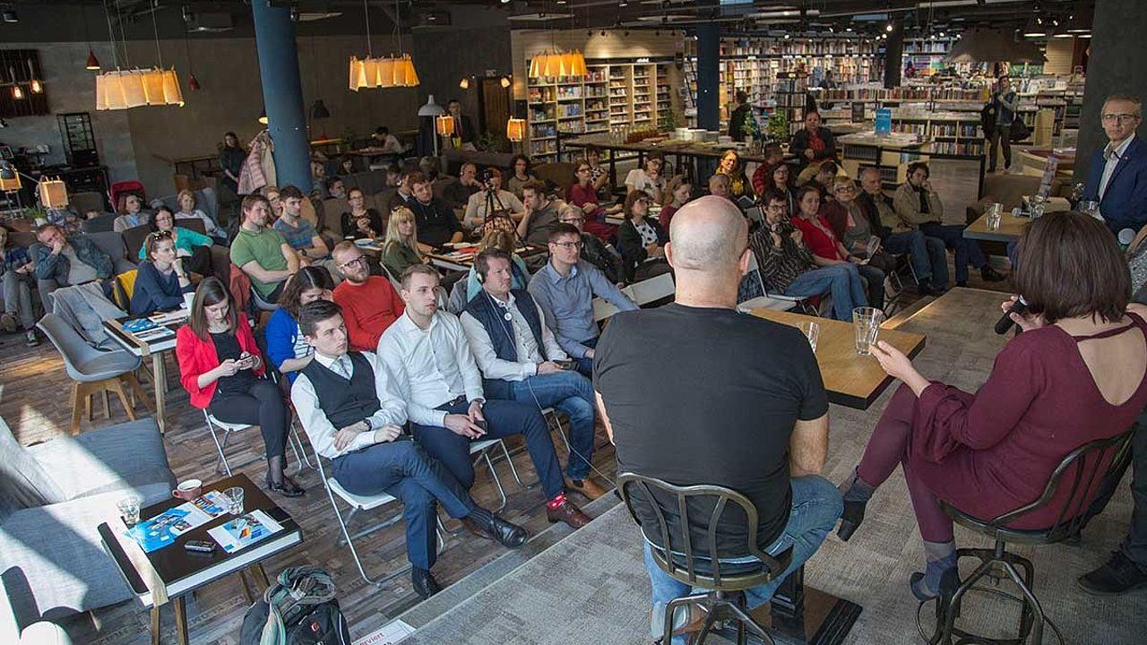 In einer Bibliothek schaut ein junges Publikum zu Diskutanten, die auf Barhockern auf der Bühne sitzten.