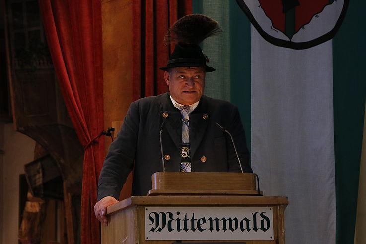 Mann mit Hut und Gamsbart am Rednerpult während seiner Rede