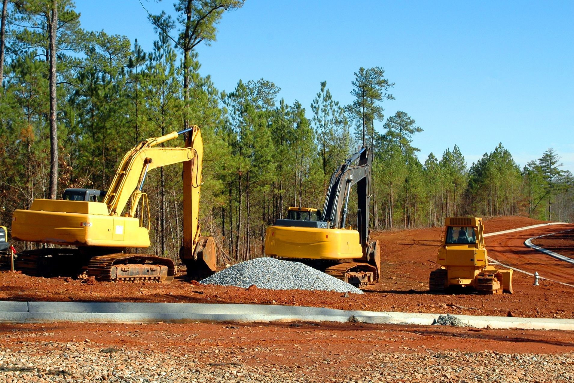 Mehrere Bagger graben am Rand eines Waldgebiets in der Erde.