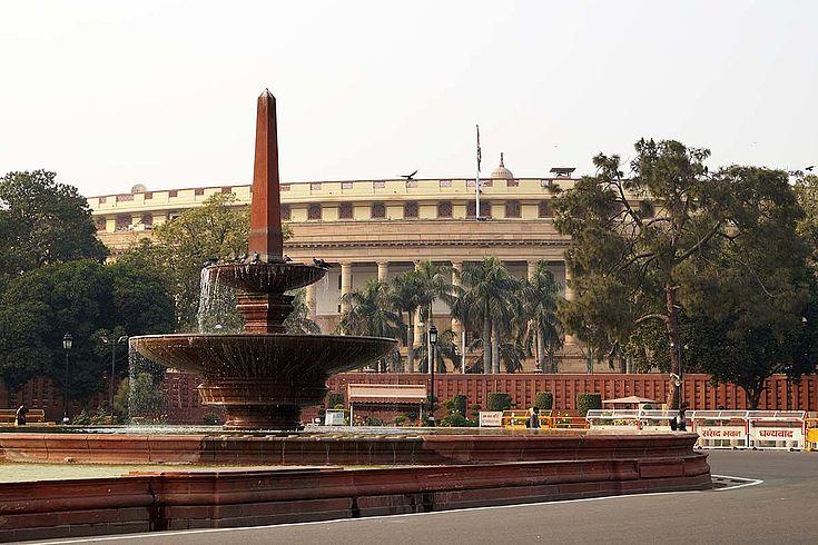 Das Parlamentsgebäue in Neu Delhi. Ein großer, runder Sandsteinbau, umgeben von einem blickdichten Zaun wie aus Containerwänden.