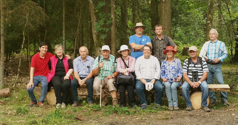 Gruppe im Wald auf einem langen Baumstumpf sitzend, erschöpft aber glücklich.