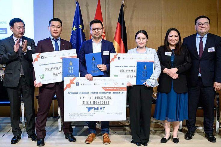 In einem Gruppenbild präsentieren drei Personen überdimensionale Glückwunschschreiben dem Publikum und im Hintergrund zu sehen sind der mongolische Botschafter in Deutschland, Dr. Ganbat Damba, eine Hauptorganisatorin des Wettbewerbs und der außenpolitische Berater des Präsidenten, Tegshjargal