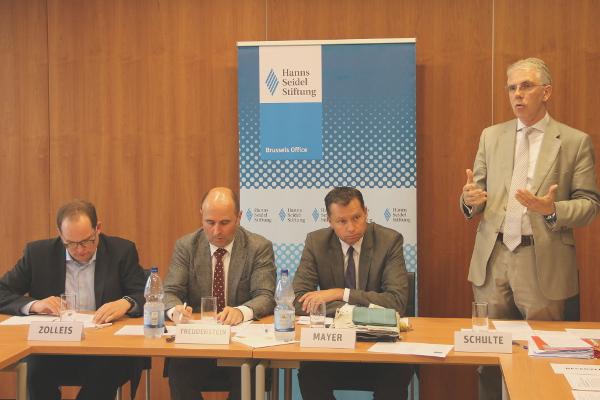 vier Männer, drei am Tisch sitzend, einer stehend und redend, im Hintergrund das Hanns-Seidel-Logo
